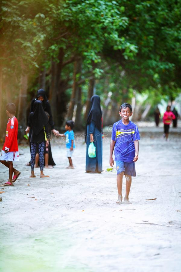 Muslim women and children are walking in the beach of island small village. Fuldhoo, Maldives - December 10, 2016: Muslim women and children are walking in the royalty free stock photo