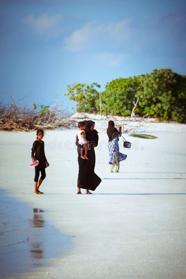 Muslim women and children are walking in the beach of island small village. Fuldhoo, Maldives - December 14, 2016: Muslim women and children are walking in the royalty free stock photography