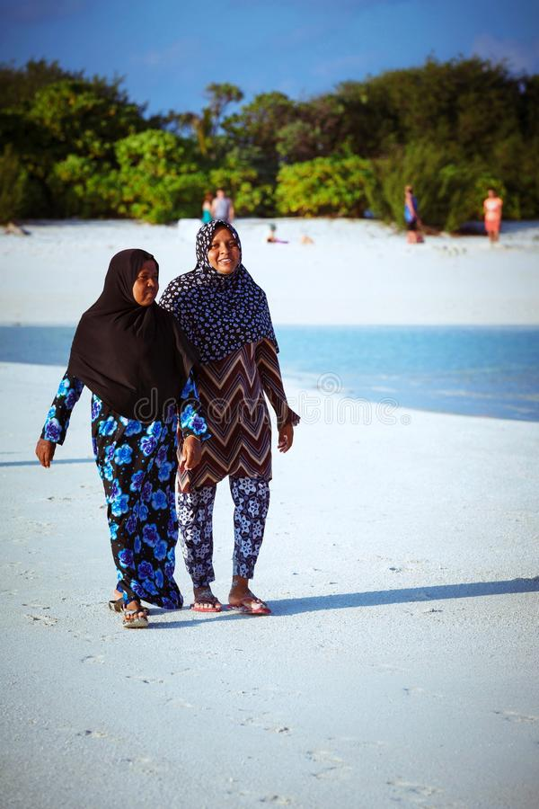 Muslim women and children are walking in the beach of island small village. Fuldhoo, Maldives - December 14, 2016: Muslim women and children are walking in the royalty free stock image