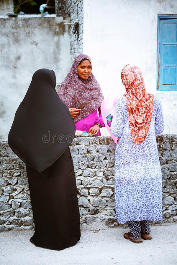 Muslim women are talking in the street of island small village. Fuldhoo, Maldives - December 10, 2016: Muslim women are talking in the street of island small stock images