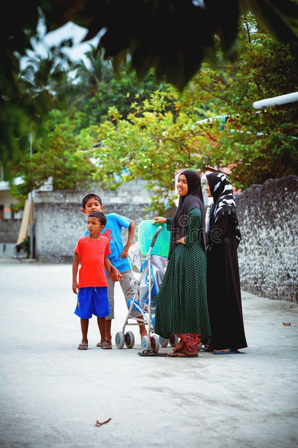Muslim women are talking in the street of island small village. Fuldhoo, Maldives - December 10, 2016: Muslim women are talking in the street of island small stock photos