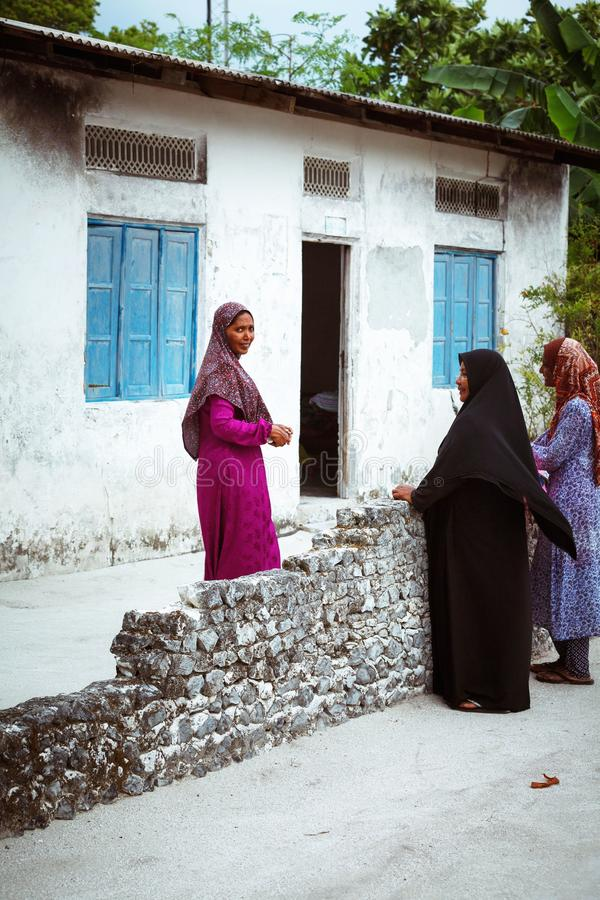 Muslim women are talking in the street of island small village. Fuldhoo, Maldives - December 10, 2016: Muslim women are talking in the street of island small royalty free stock image