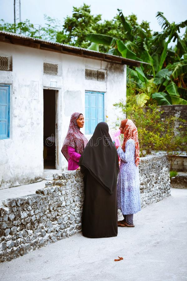 Muslim women are talking in the street of island small village. Fuldhoo, Maldives - December 10, 2016: Muslim women are talking in the street of island small royalty free stock photos