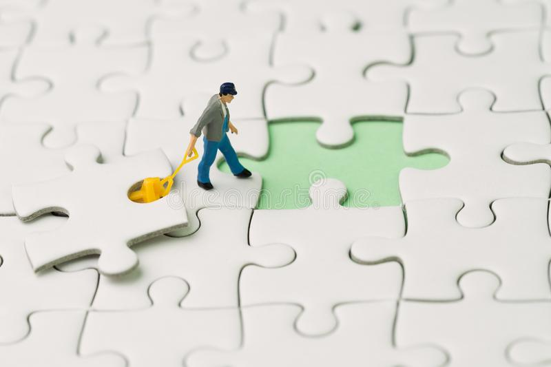 Fulfill the missing piece for business success strategy metaphor. Miniature worker figurine using the forklift to complete the last white jigsaw puzzle piece stock images