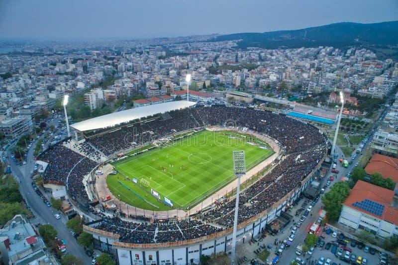 Fuliggine aerea dello stadio di Toumba in pieno dei fan durante la partita di calcio per il campionato fra il PAOK dei gruppi con fotografie stock libere da diritti
