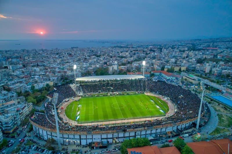 Fuliggine aerea dello stadio di Toumba in pieno dei fan durante la partita di calcio per il campionato fra il PAOK dei gruppi con immagine stock