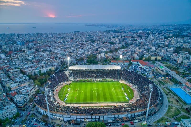 Fuliggine aerea dello stadio di Toumba in pieno dei fan durante la partita di calcio per il campionato fra il PAOK dei gruppi con fotografia stock