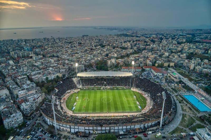 Fuliggine aerea dello stadio di Toumba in pieno dei fan durante la partita di calcio per il campionato fra il PAOK dei gruppi con fotografia stock libera da diritti