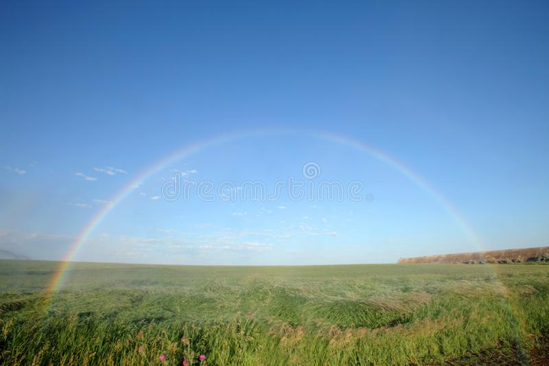 A full arch rainbow showing both ends. stock photo