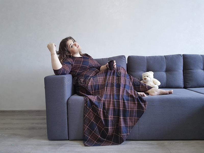 Full beautiful girl on the couch sits with a cup stock images