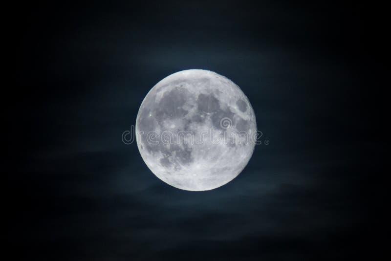 Full blå måne som visas på natten till och med mellanrum i de mörka molnen royaltyfri bild