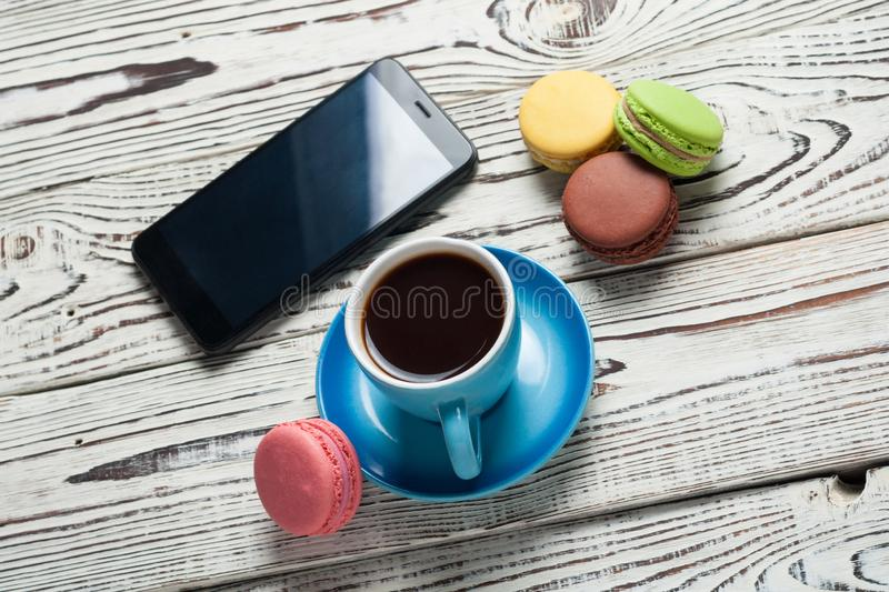Full blue cup of black coffee near mobile phone and scattered colorful whole macaroons on old rustic weathered wooden table. Full blue cup of black coffee near stock images