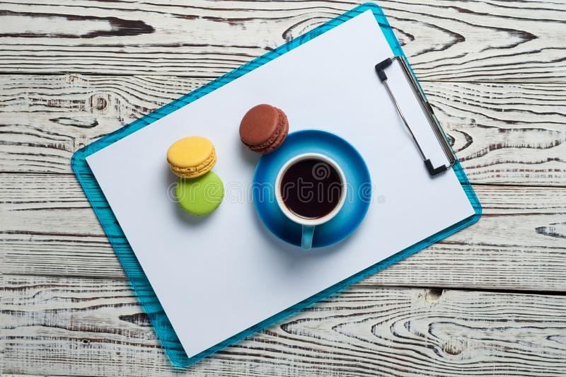 Full blue cup of black coffee near plastic clipboard with blank paper sheets beside scattered colorful whole macaroons royalty free stock image