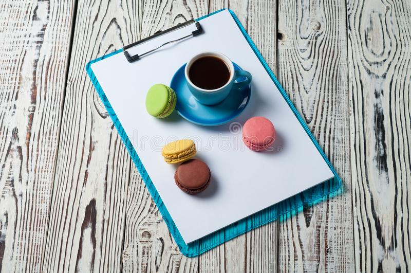 Full blue cup of black coffee near plastic clipboard with blank paper sheets beside scattered colorful whole macaroons royalty free stock images