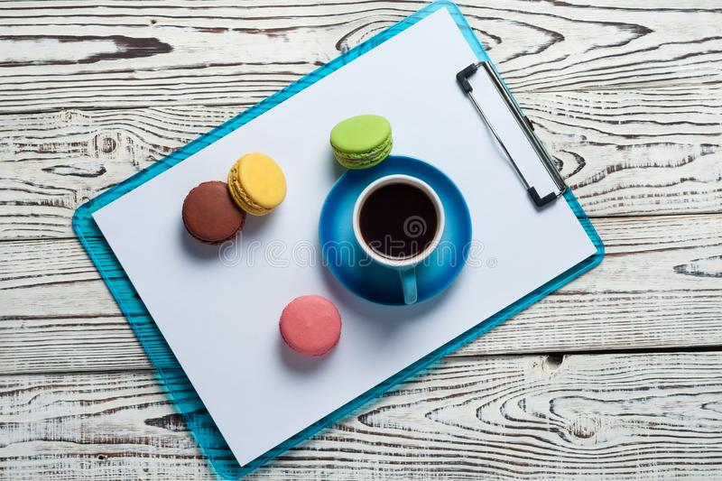 Full blue cup of black coffee near plastic clipboard with blank paper sheets beside scattered colorful whole macaroons royalty free stock photography