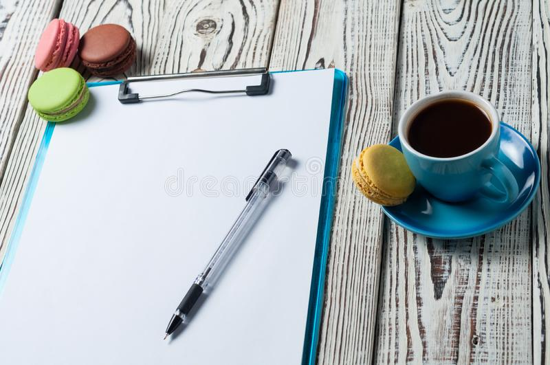 Full blue cup of black coffee near plastic clipboard with blank paper sheets beside scattered colorful whole macaroons and pen stock photography