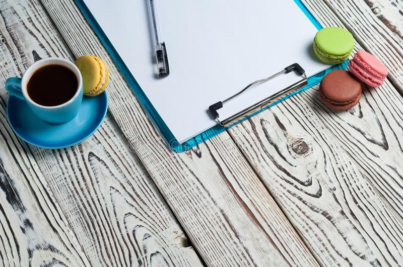 Full blue cup of black coffee near plastic clipboard with blank paper sheets beside scattered colorful whole macaroons and pen stock photos