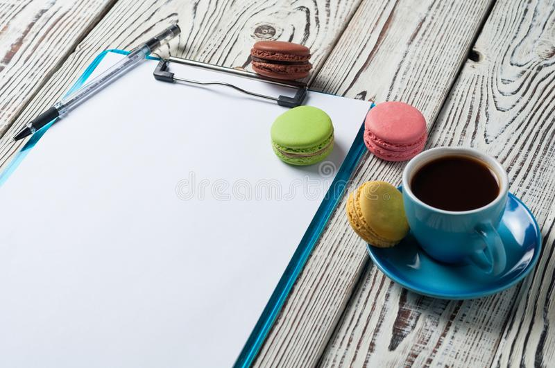 Full blue cup of black coffee near plastic clipboard with blank paper sheets beside scattered colorful whole macaroons and pen royalty free stock photography