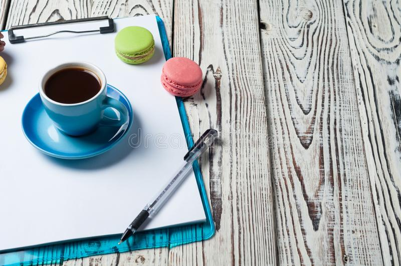 Full blue cup of black coffee near plastic clipboard with blank paper sheets beside scattered colorful whole macaroons and pen stock images