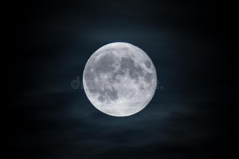 Full blue moon appearing at night through gaps in the dark clouds. royalty free stock image