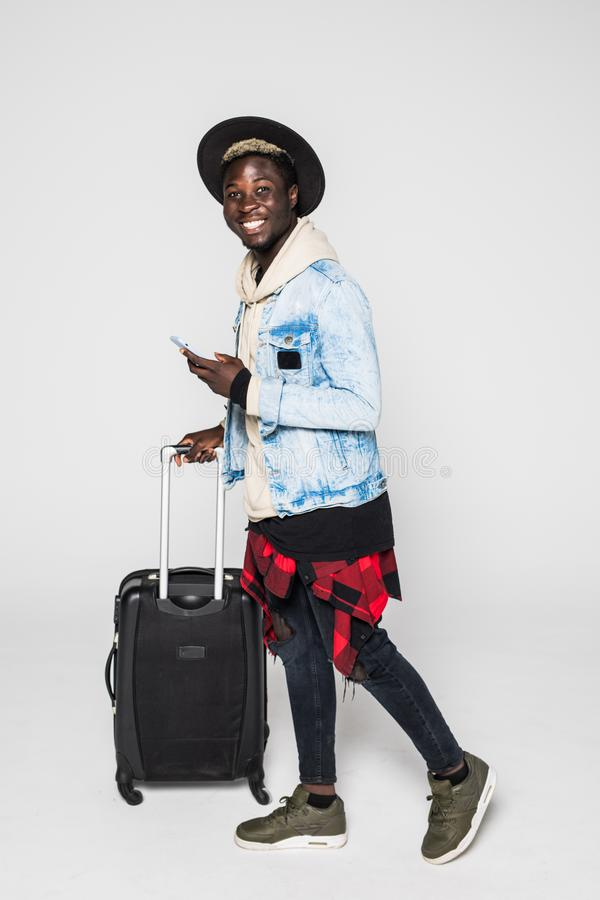 Full body of African american business man traveling with suitcases walking on white background stock image