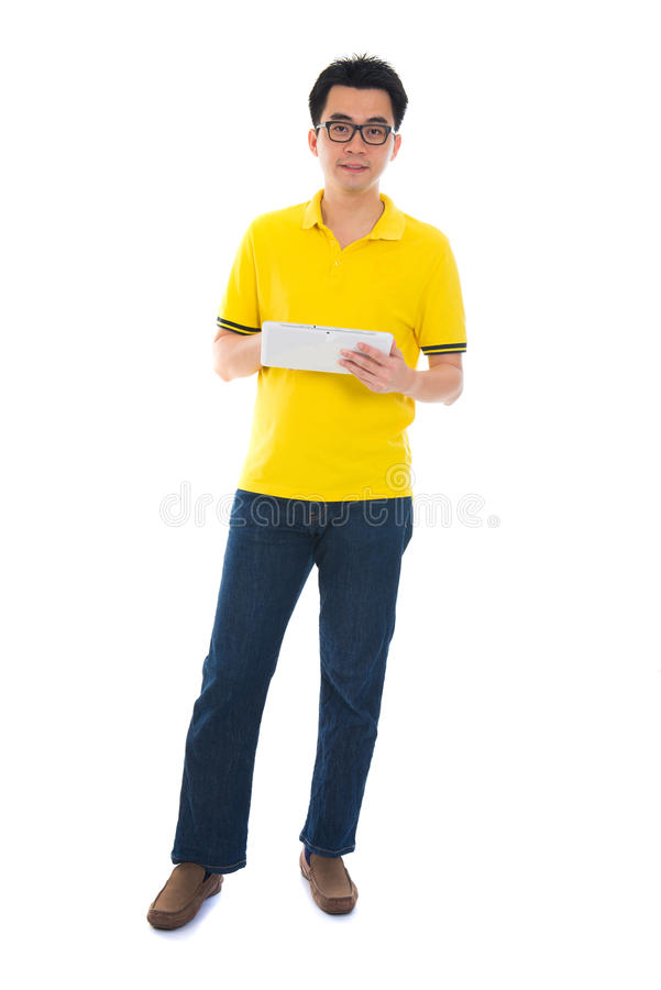 Full body Asian adult student in casual wear with school bag using digital computer tablet pc standing isolated on white stock photography