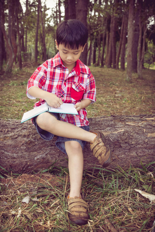 Full body. Asian boy writing on notebook. Education concept. Vintage style. stock photography