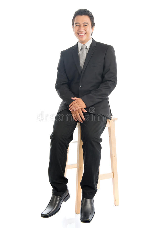 Full body Asian businessman sitting on chair royalty free stock photography