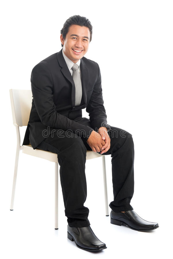 Full body Asian businessman sitting on white chair stock photo