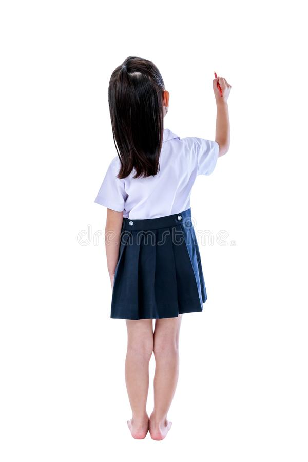 Asian girl writing something with red crayon. Isolated on white. Full body. Back view of young preschool child in uniform. Asian girl writing something with red stock photos