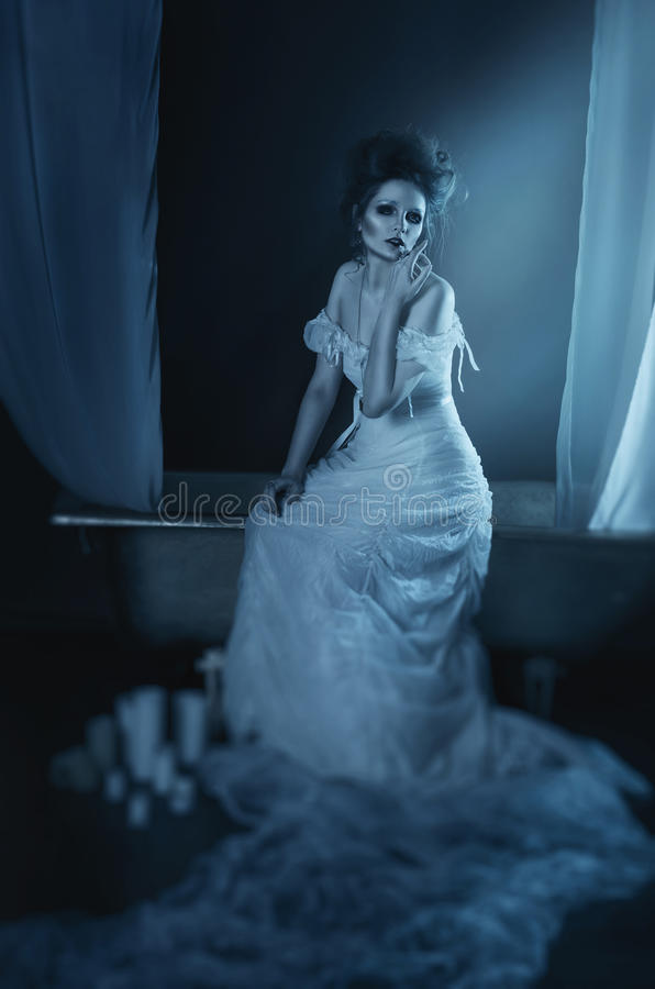full body beautiful girl ghost, witch, bride sitting on a vintage copper bath with a white canopy, in a long white dress with stock photography