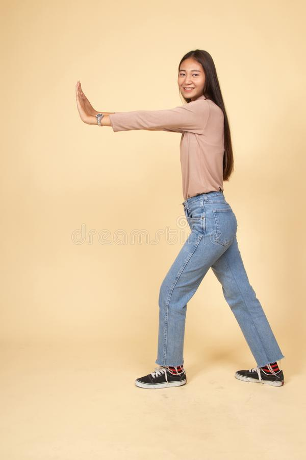 Full body of beautiful young asian woman push something. On beige background stock photo