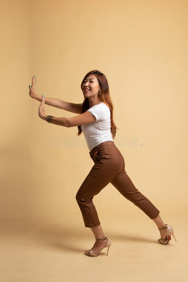 Full body of beautiful young asian woman push something. On beige background royalty free stock images