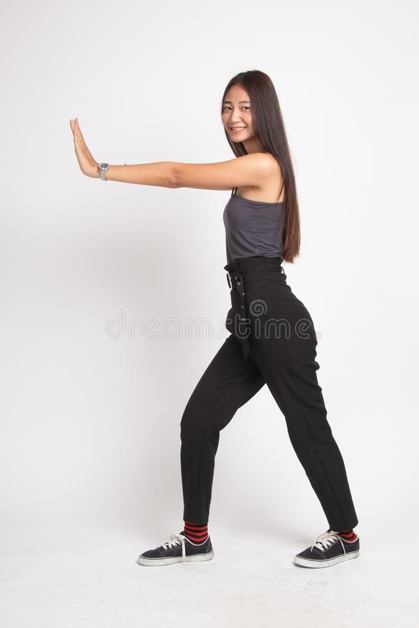 Full body of beautiful young asian woman push something. On white background royalty free stock photo