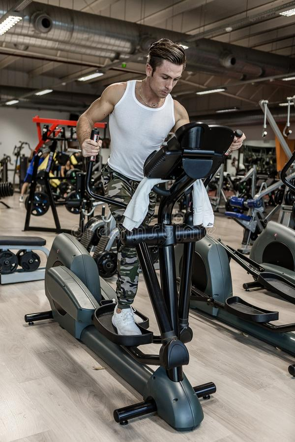 Strong guy exercising on step machine stock images
