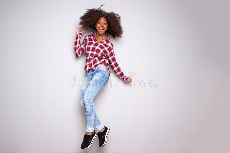 Full body excited young black woman jumping with joy over white background stock photography