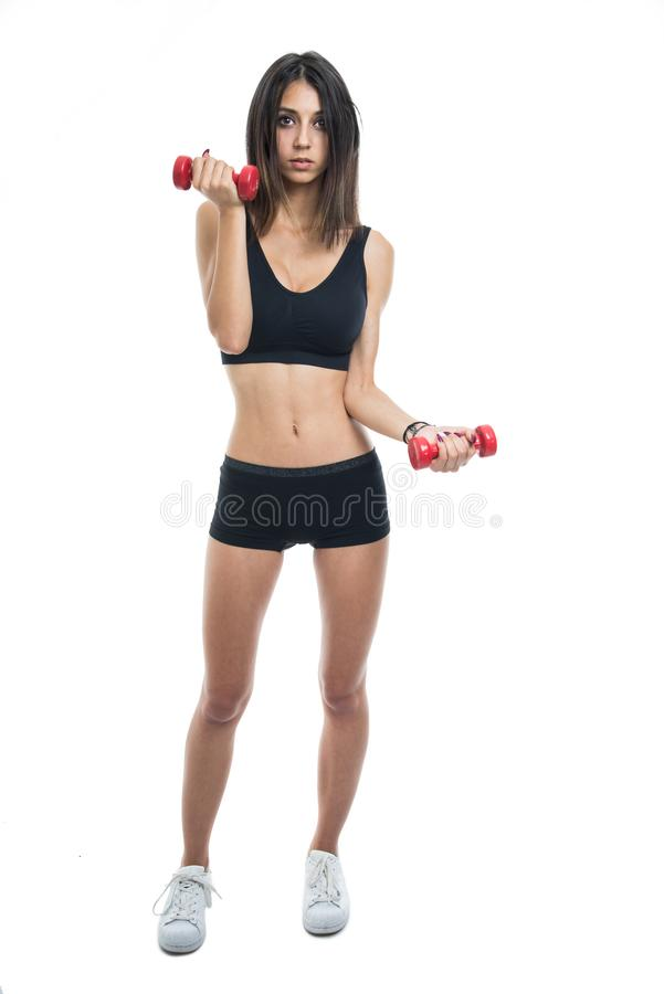 Full body of fit girl exercising with dumbbells stock image