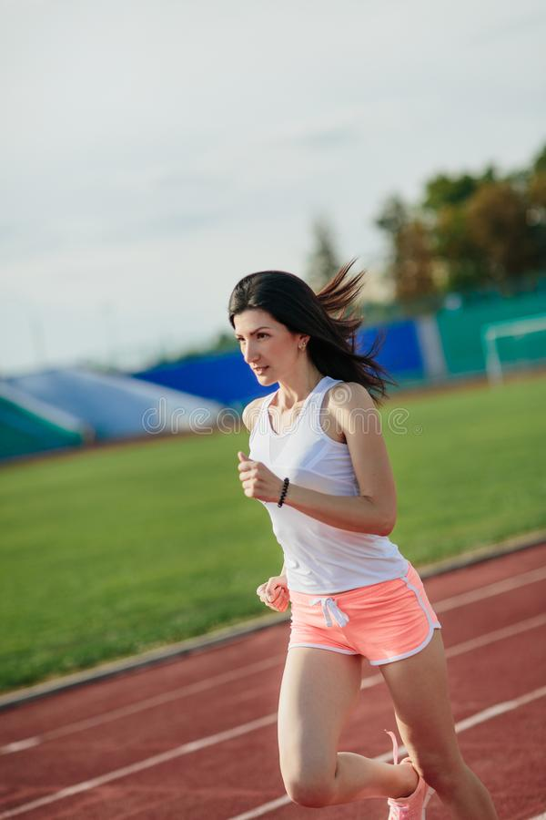 Portrait of girl running track on stadium. Real front view of young woman in pink shorts and tank top and pink sneakers. Outdoors. Full body of girl running stock images