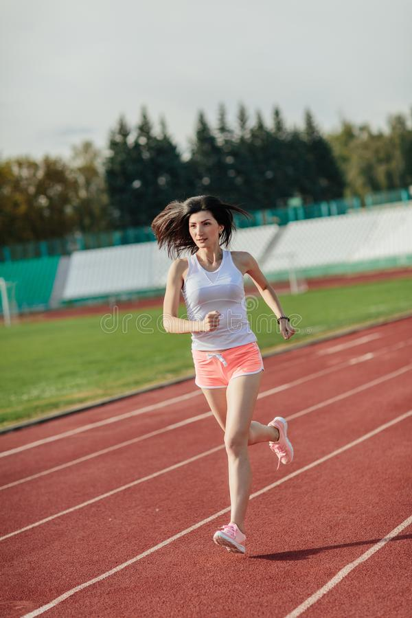 Full body of girl running track on stadium. Real front view of young woman in pink shorts and tank top and pink sneakers. Outdoors. Young woman in pink shorts stock photos