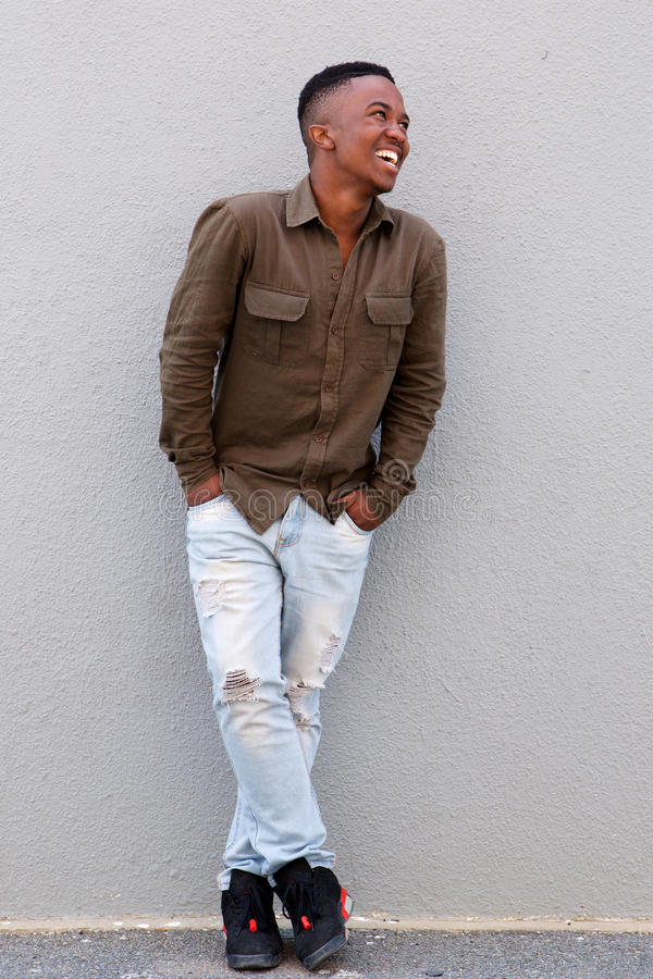 Full body happy black man leaning against gray wall royalty free stock photography