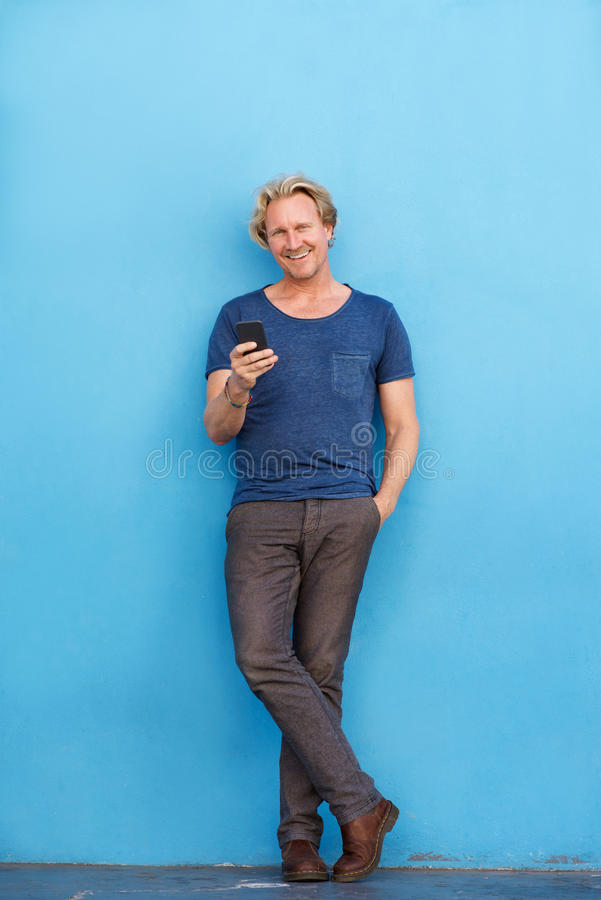 Full body happy man standing by wall with mobile phone stock images