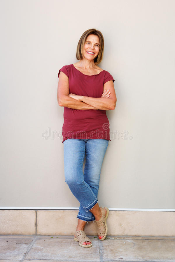 Full body happy older woman leaning against wall royalty free stock images