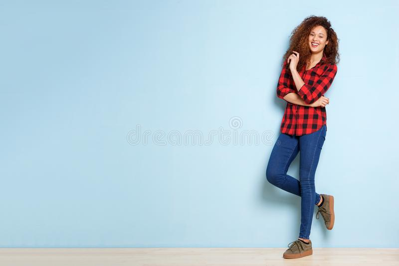 Full body happy woman with curly hair leaning against blue background royalty free stock images