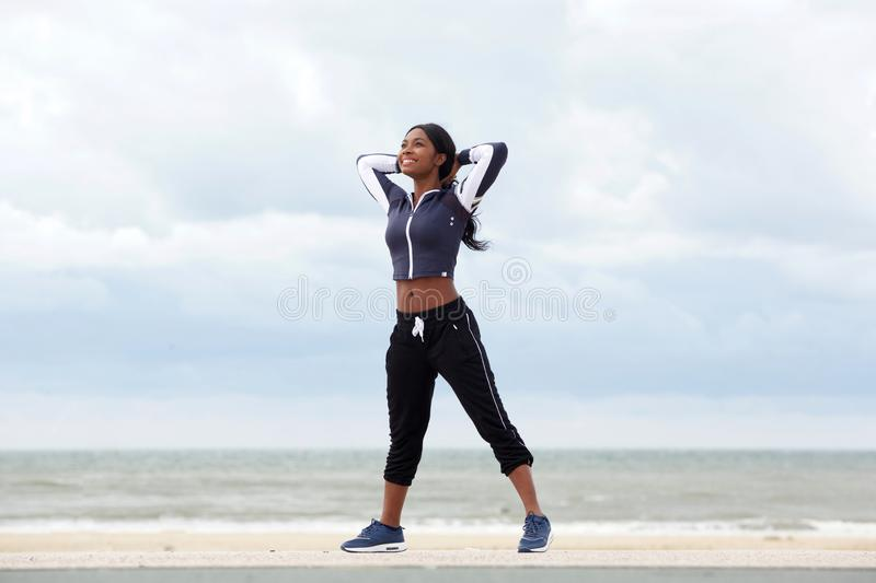 Full body healthy african american woman relaxing with hands behind head at beach royalty free stock photography