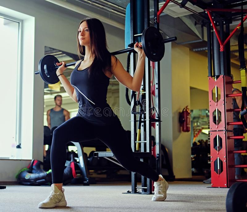 Image of sporty brunette female doing squats with barbell in a gym club. royalty free stock images
