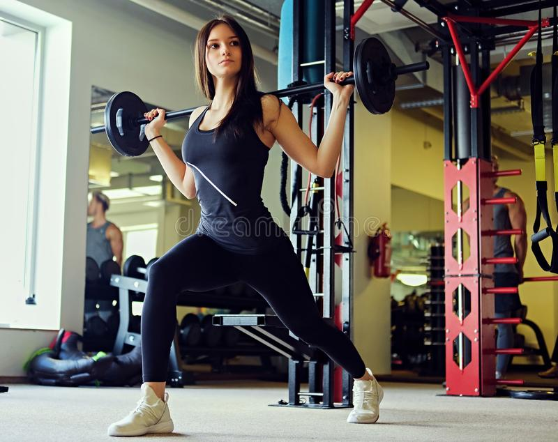 Image of sporty brunette female doing squats with barbell in a gym club. royalty free stock image