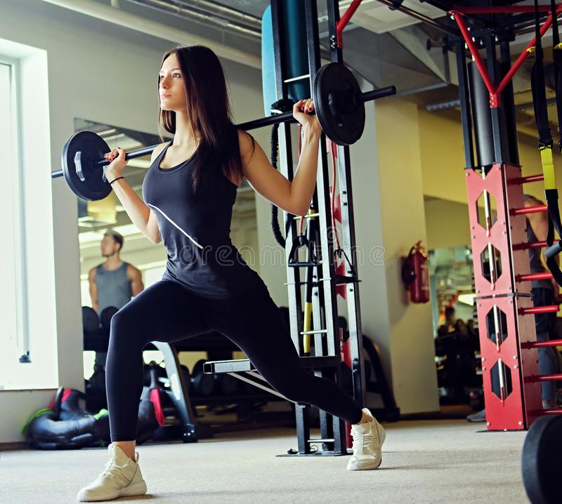 Image of sporty brunette female doing squats with barbell in a gym club. royalty free stock photography