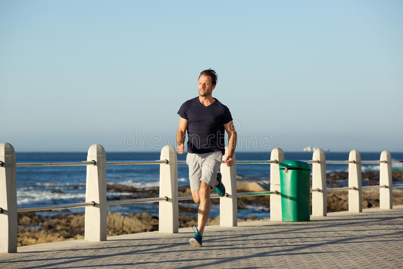 Full body middle age sports man running outside royalty free stock images