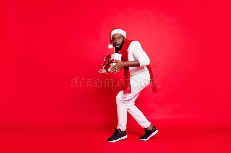 Full body photo of dark skin man making newyear surprise for family going tiptoe carry giftbox under x-mas tree wear. Sweater trousers, santa hat  red stock photo