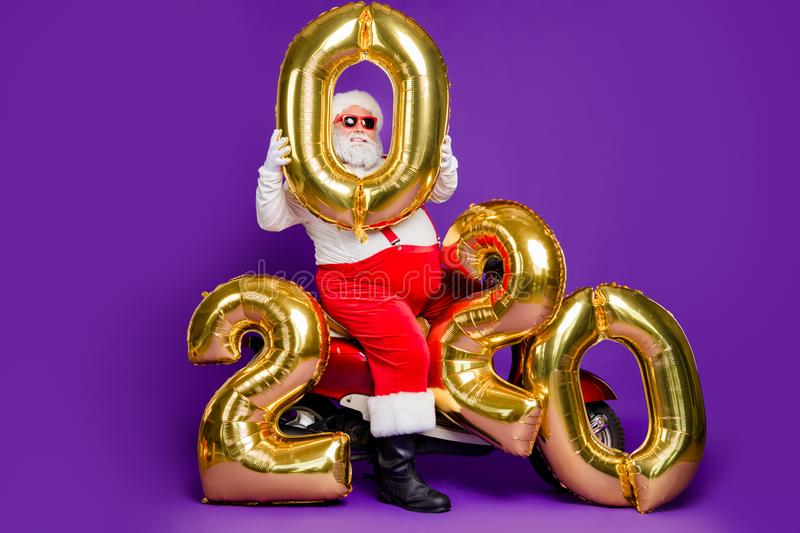 Full body photo of fat santa man sitting on bike holding big air newyear 2020 numbers balloons congratulating people. Full body photo of fat santa man sitting on stock images